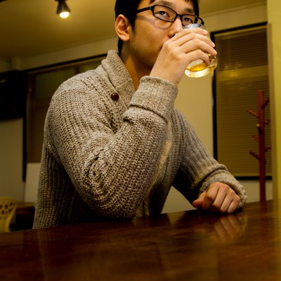 バーでグラスを持つデザイナーの写真