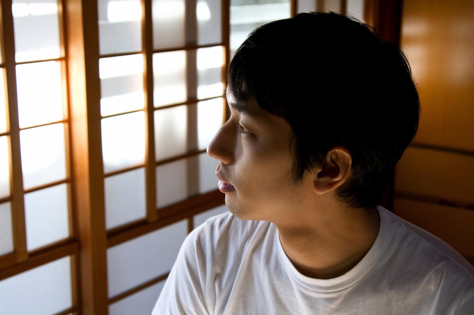 「和室から外を見つめる男性」の写真[モデル:大川竜弥]