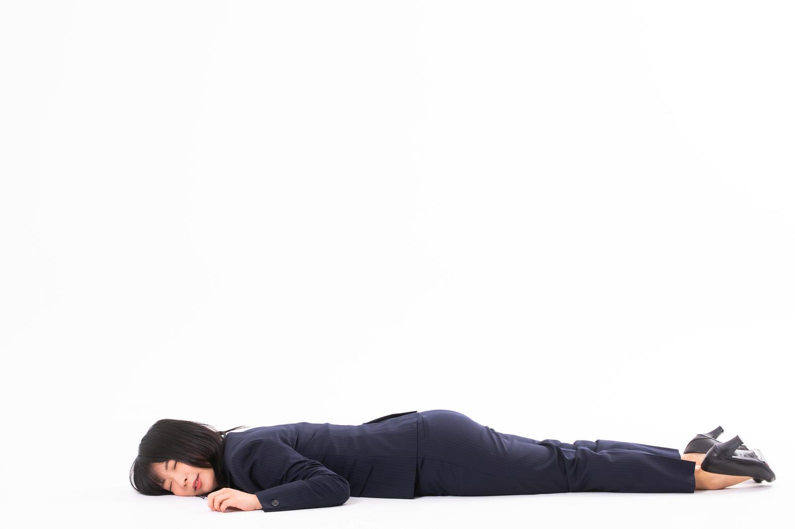 「倒れながら爆睡する社畜女子」の写真[モデル:にゃるる]