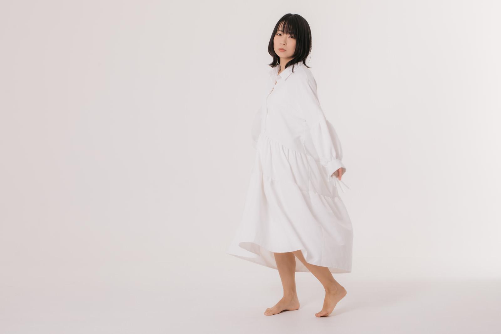 「寂しげな表情で見つめる白いワンピースの女性」の写真[モデル:にゃるる]