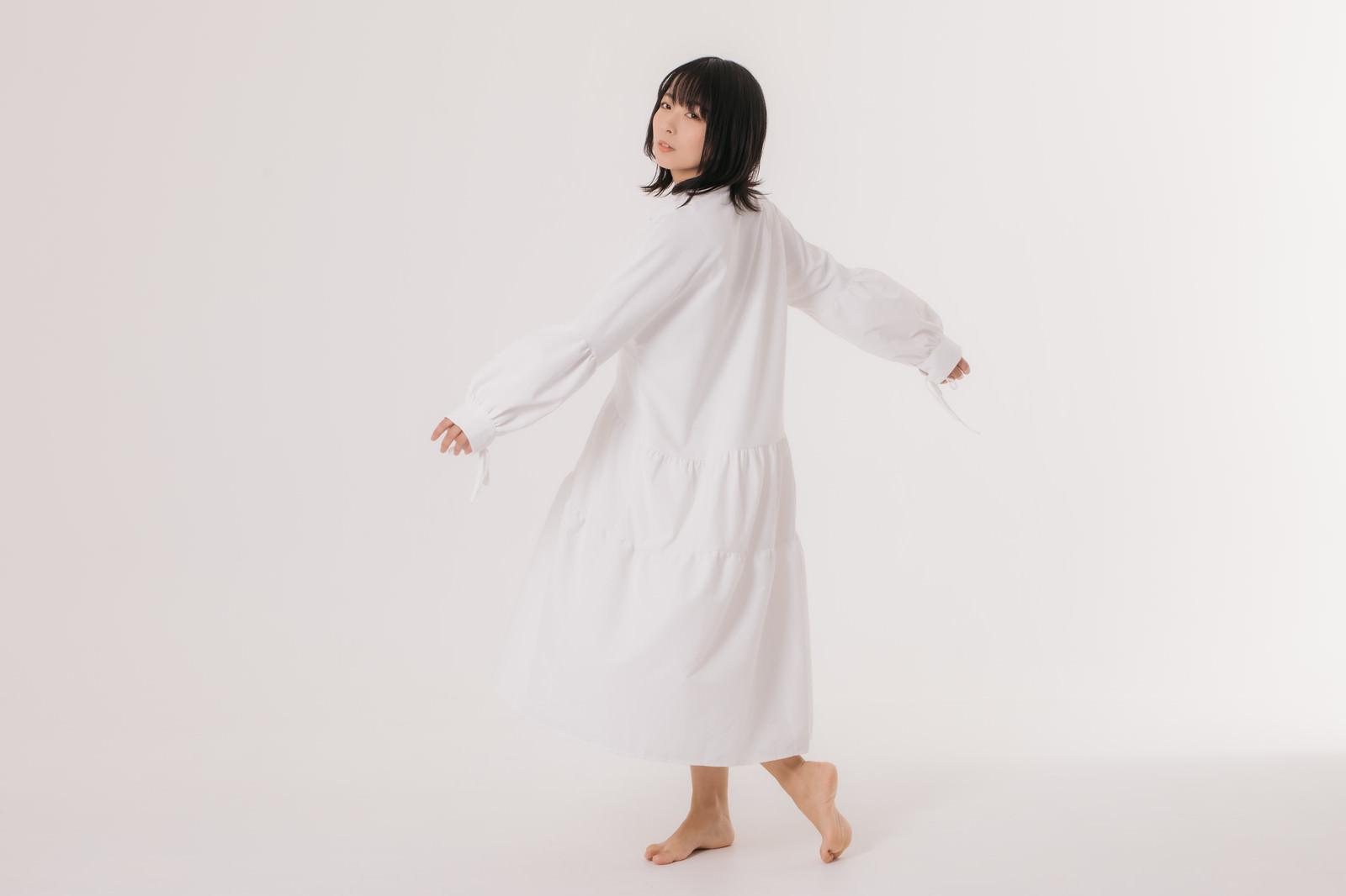 「少し大きめのワンピを着て振り返る女性モデル」の写真[モデル:にゃるる]