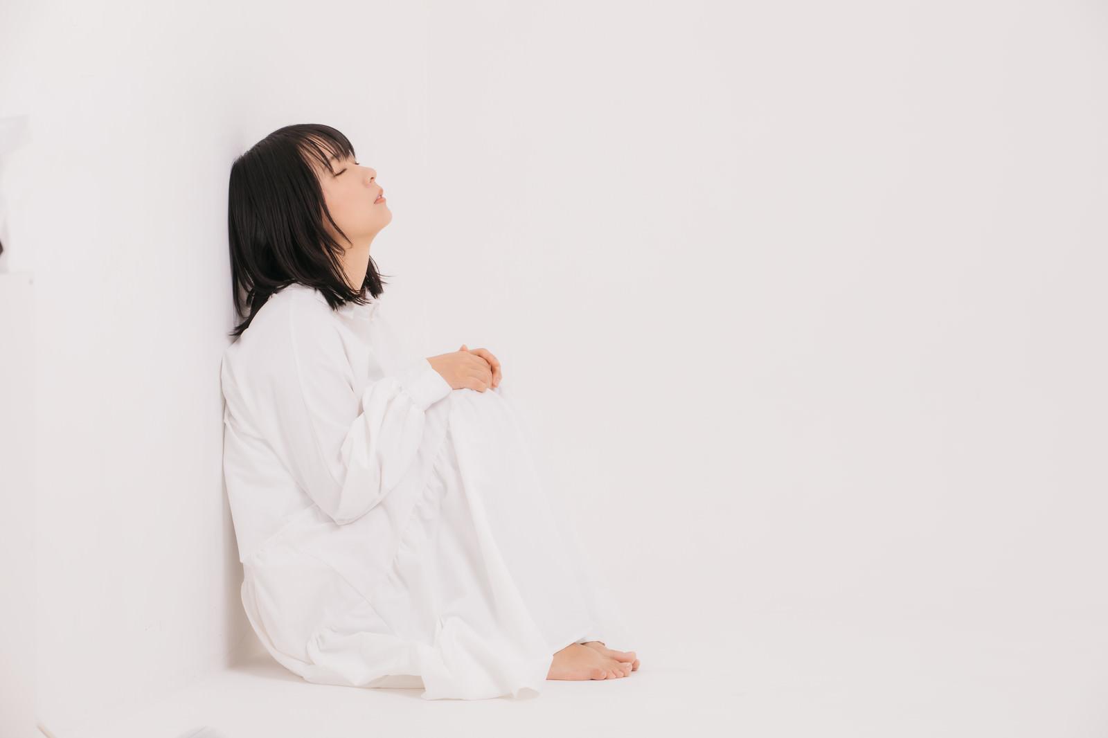 「壁に寄りかかって寝落ちする女性」の写真[モデル:にゃるる]