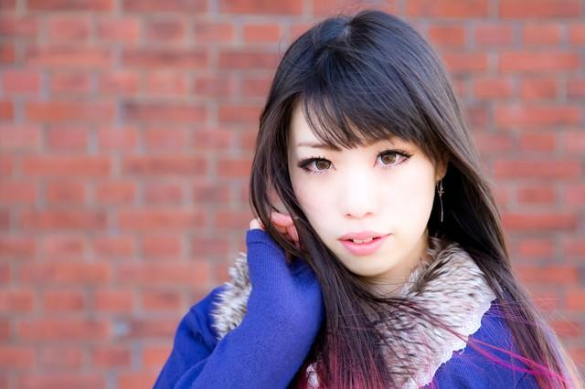 赤レンガで髪をかきあげる女性の写真