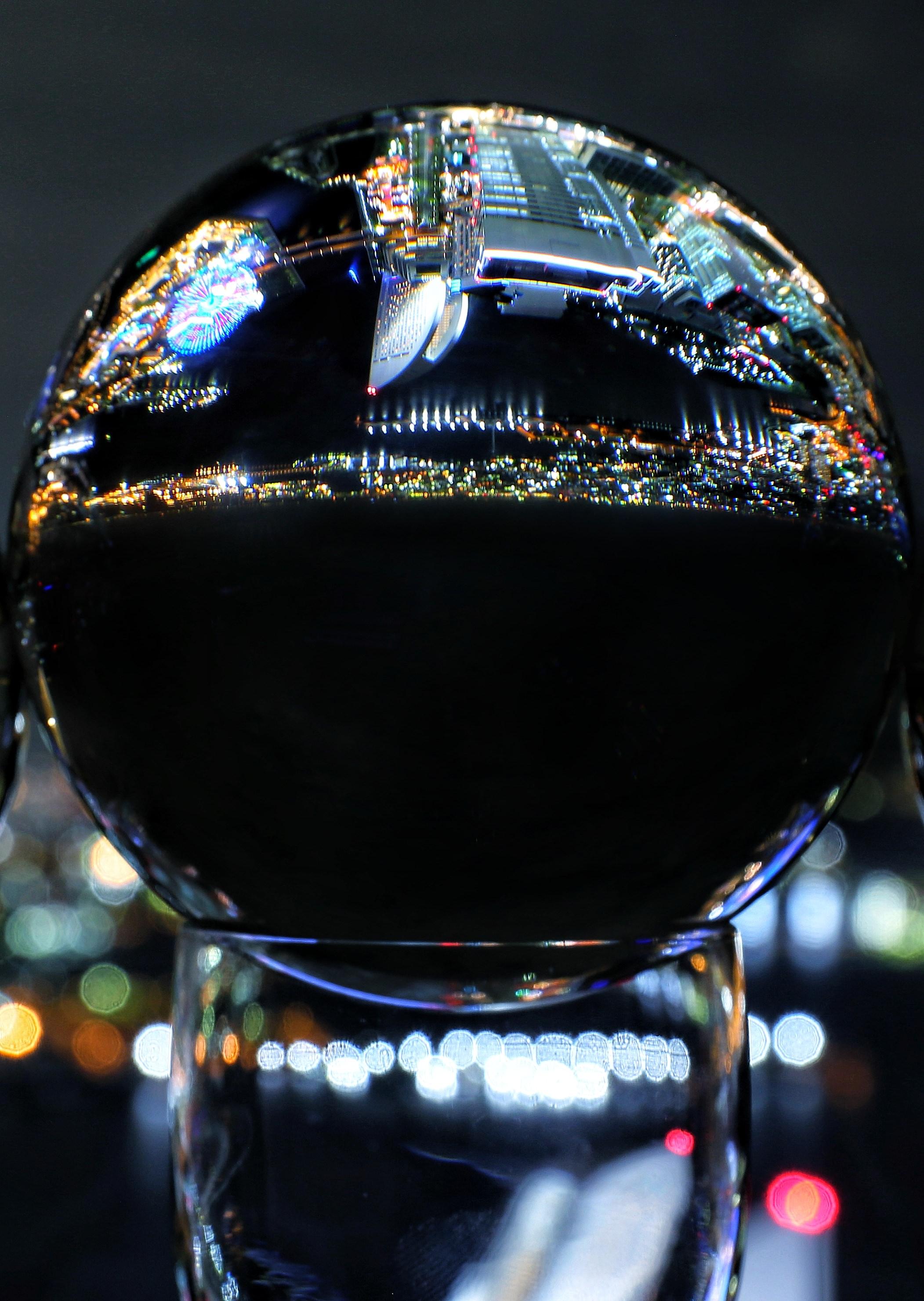 「水晶玉に映り込む都会の夜景」の写真
