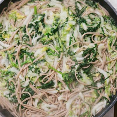 「鍋にお湯を沸かしてそばと大根、白菜、ほうれん草を加える」の写真素材