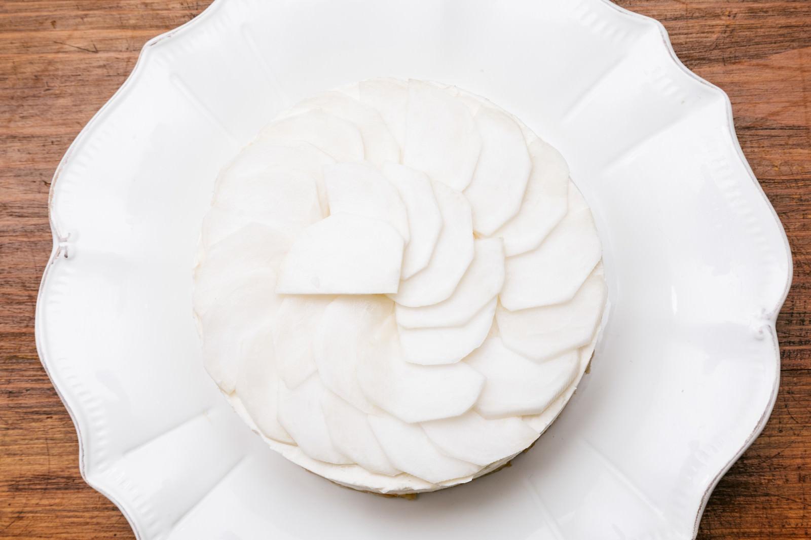 「薄切りにしたかぶをケーキに載せる薄切りにしたかぶをケーキに載せる」のフリー写真素材を拡大