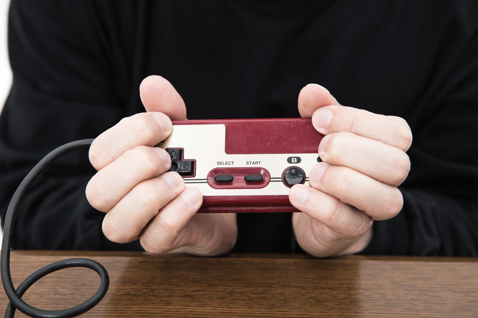 「ファミコンのコントローラーでAC持ち(ヘンタイグリップ)」の写真[モデル:大川竜弥]