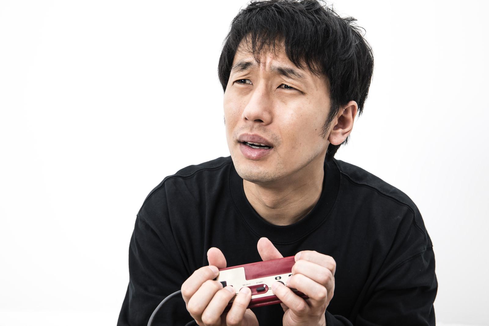 「こんなコントローラーの持ち方じゃうまくプレイできないと涙目のゲーマー」の写真[モデル:大川竜弥]