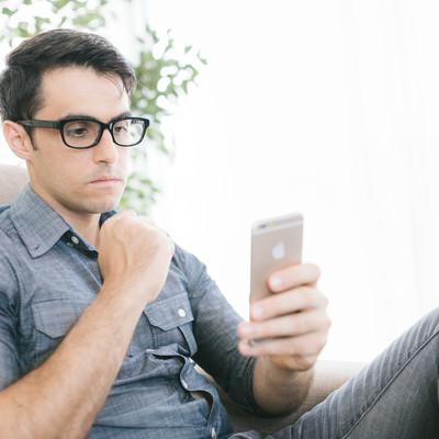 ニュースを見て不安な気持ちになる男性の写真