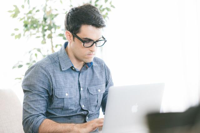 明るいオフィスでコーディング中のエンジニアの写真