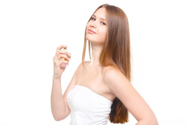香水と横目線の微笑む女性の写真