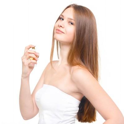 「香水と横目線の微笑む女性」の写真素材