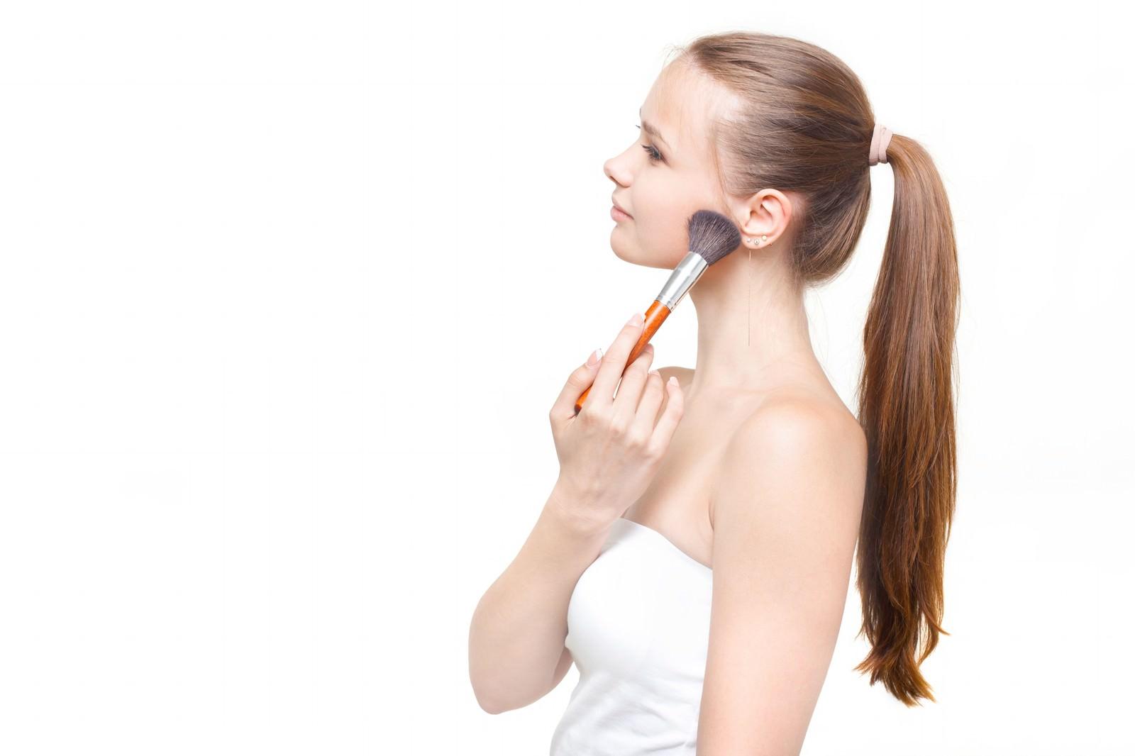 「顎にチークブラシを当てる横顔の外国人女性」の写真[モデル:モデルファクトリー]