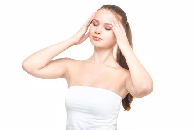 両手を顔肌に目を瞑る女性の写真