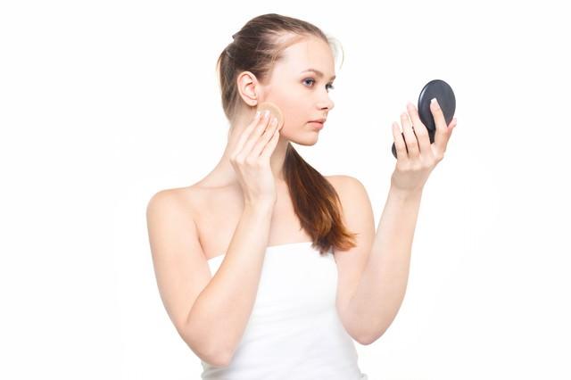 コンパクトミラーを見ながら真剣な表情で化粧をする女性の写真