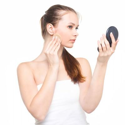 「コンパクトミラーを見ながら真剣な表情で化粧をする女性」の写真素材