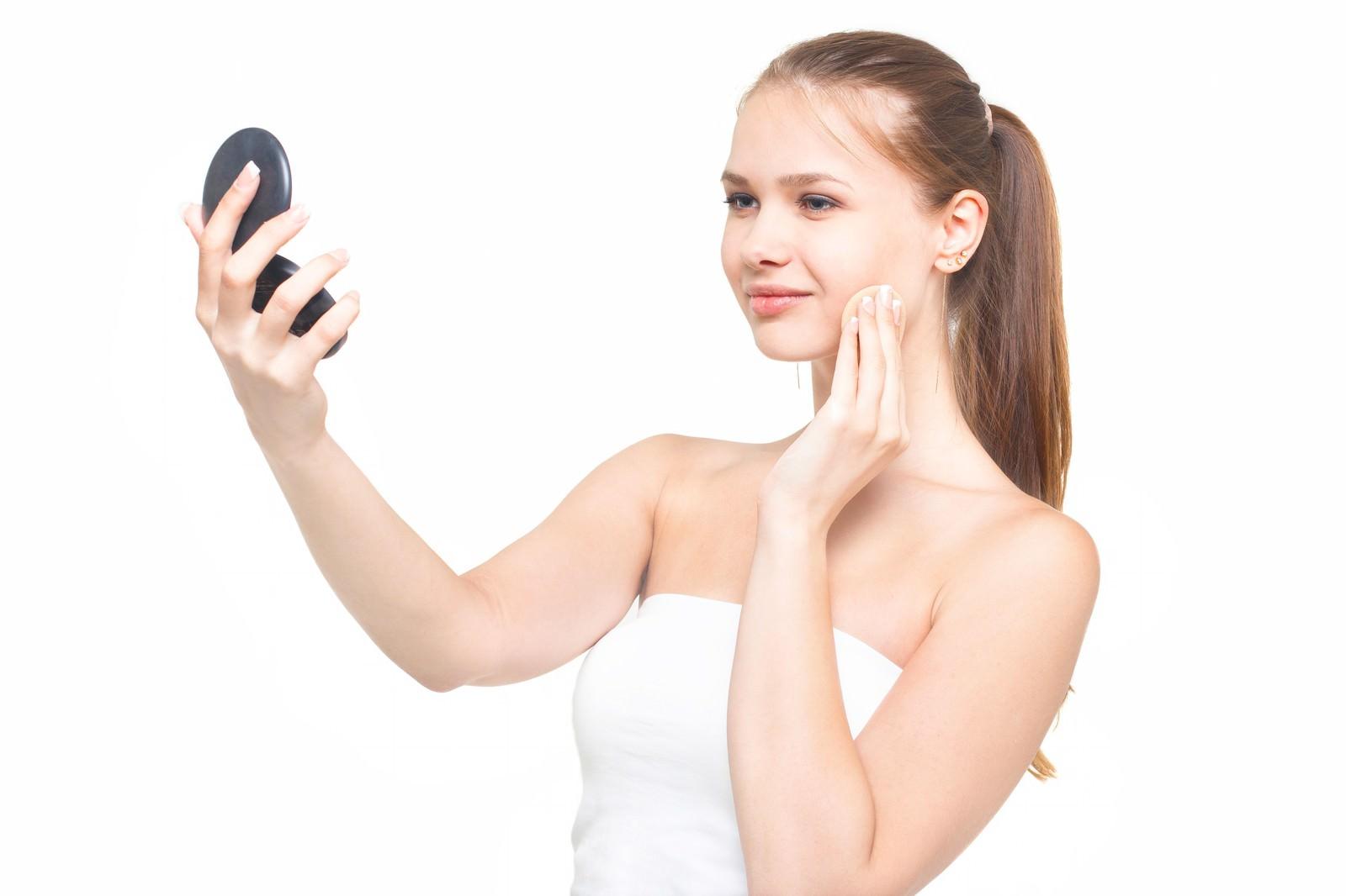 「コンパクトミラーを見ながら化粧をする微笑み顔の女性」の写真[モデル:モデルファクトリー]