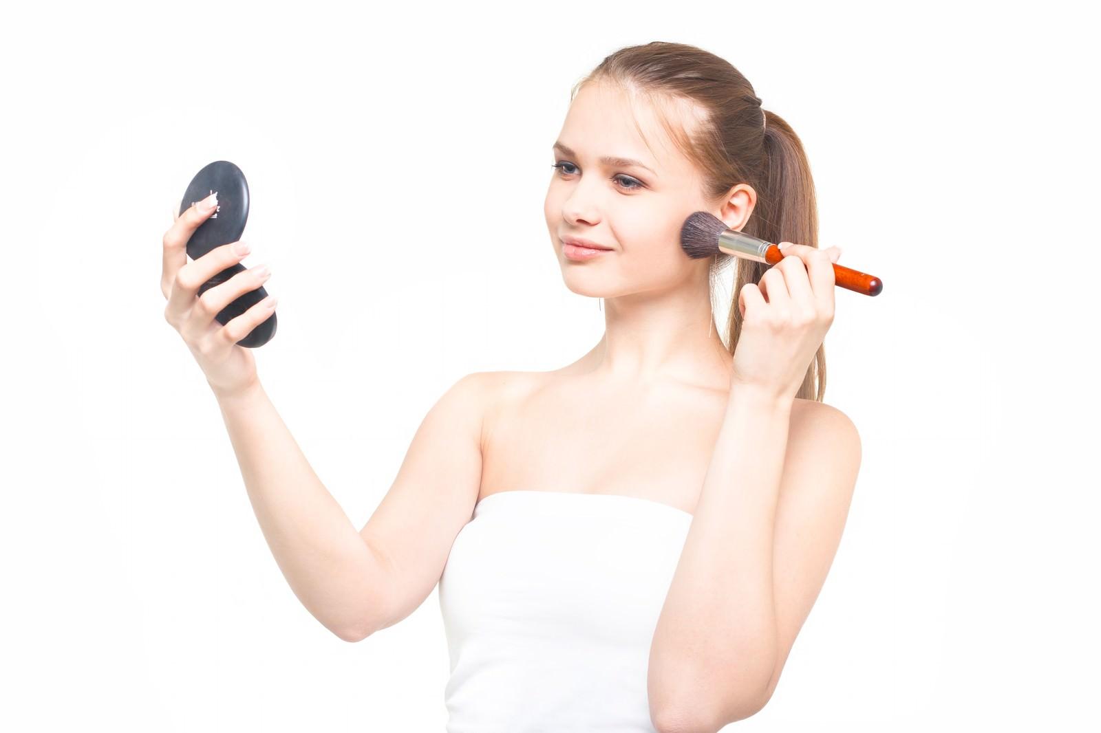 「コンパクトミラーを持ちながらチークブラシでメイクする外国人女性」の写真[モデル:モデルファクトリー]