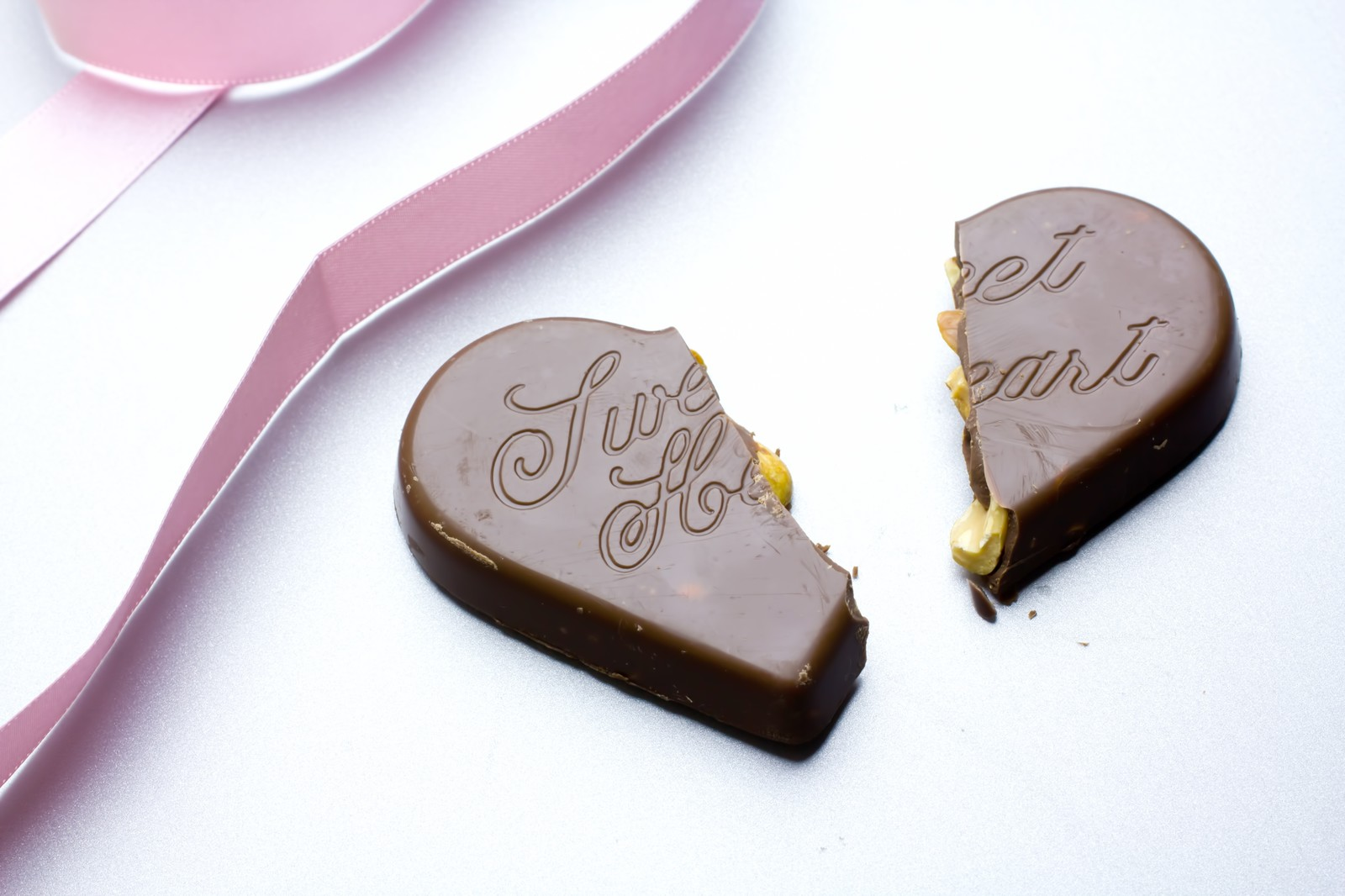 「真っ二つに割れたハートのチョコレートとリボン」の写真