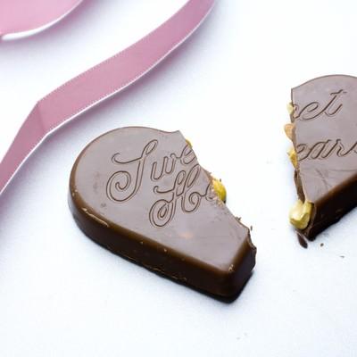 真っ二つに割れたハートのチョコレートとリボンの写真