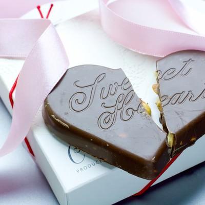 「プレゼントされた箱と割れたハートのチョコ」の写真素材