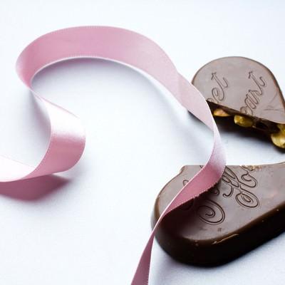 ピンクのリボンと割れたチョコレートの写真