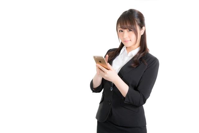 スマホでアポを確認する女性従業員の写真