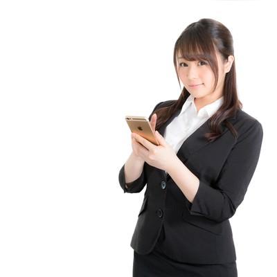 「スマホでアポを確認する女性従業員」の写真素材