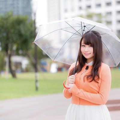 「雨の中、今日の天気を伝えるお姉さん」の写真素材