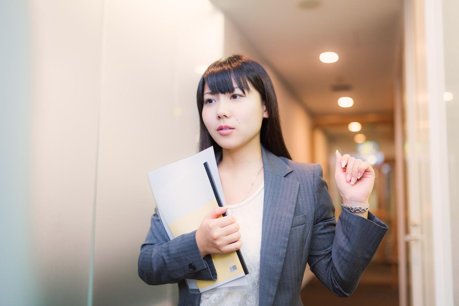 「資料を抱え会議室に向かう女性社員」の写真[モデル:Lala]