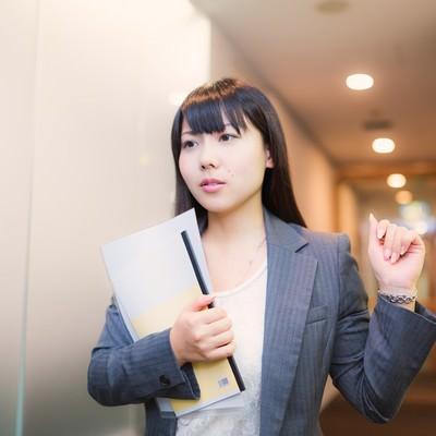 「資料を抱え会議室に向かう女性社員」の写真素材