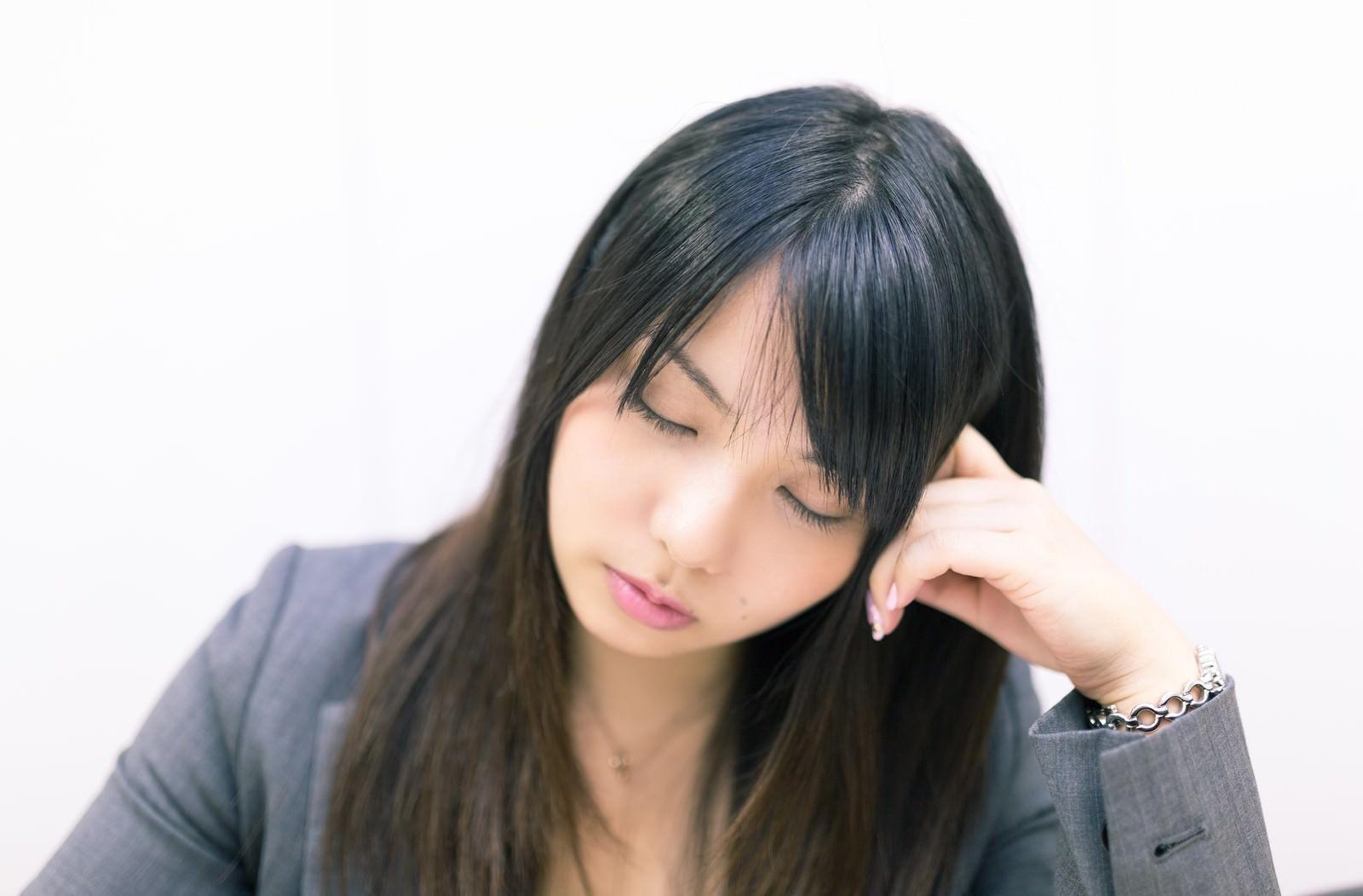 「考えこむフリをして会議中堂々と居眠りをする女性社員」の写真[モデル:Lala]