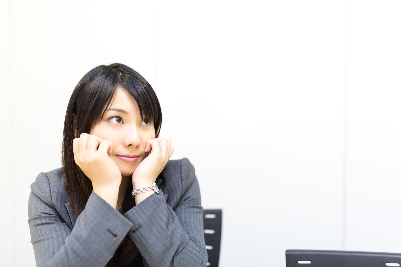 「会議中、上目づかいで上司のプレゼンを見守る女性社員」の写真[モデル:Lala]