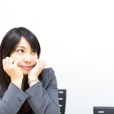 「会議中、上目づかいで上司のプレゼンを見守る女性社員」の写真素材