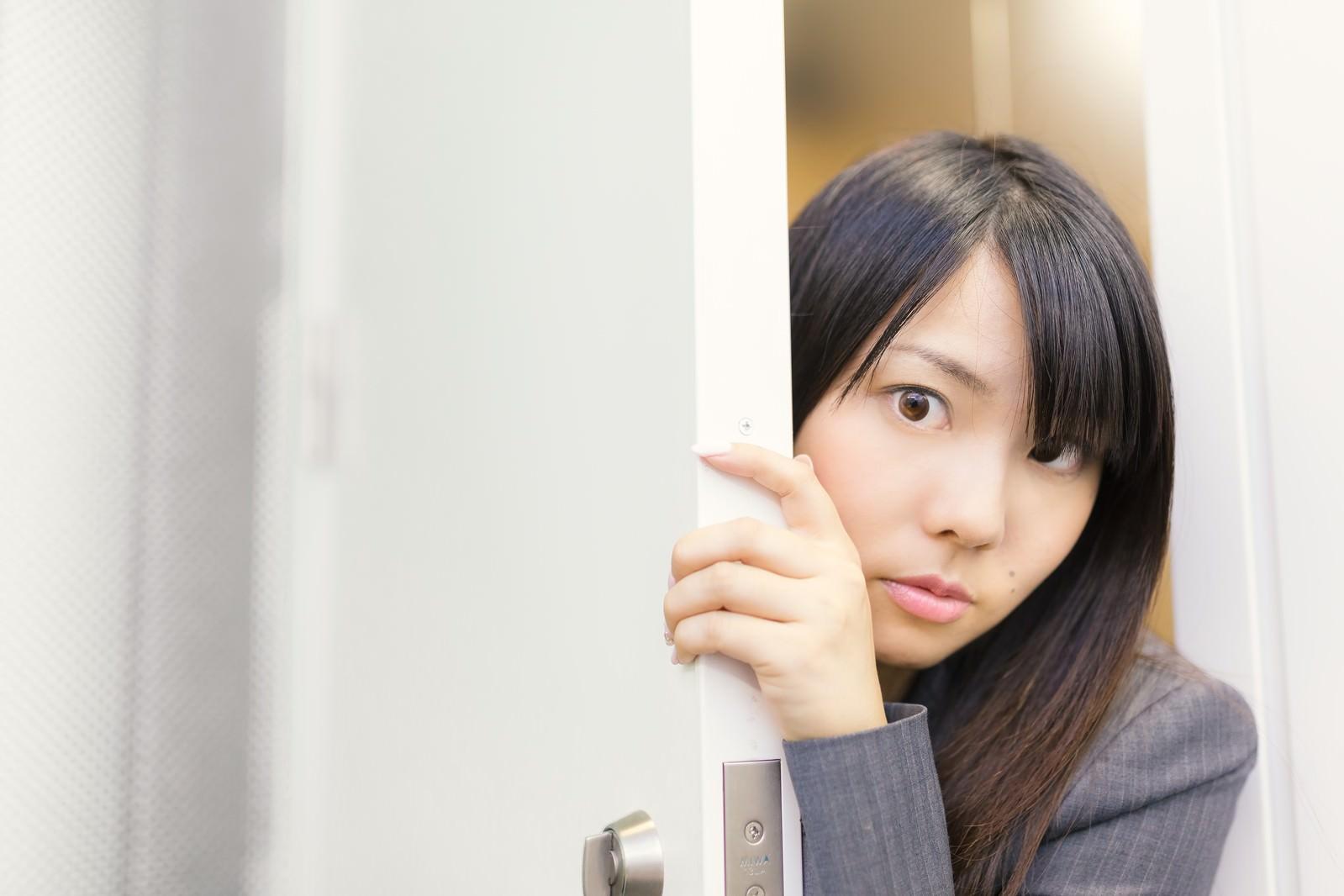 「会議の様子をドアの隙間から覗く女性社員」の写真[モデル:Lala]