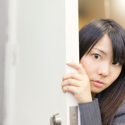 「会議の様子をドアの隙間から覗く女性社員」の写真素材