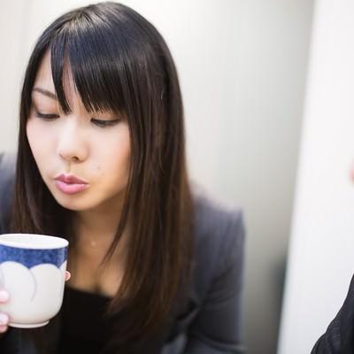 「フーフーしてお茶を冷まし来客の胸を熱くする女性社員」の写真素材