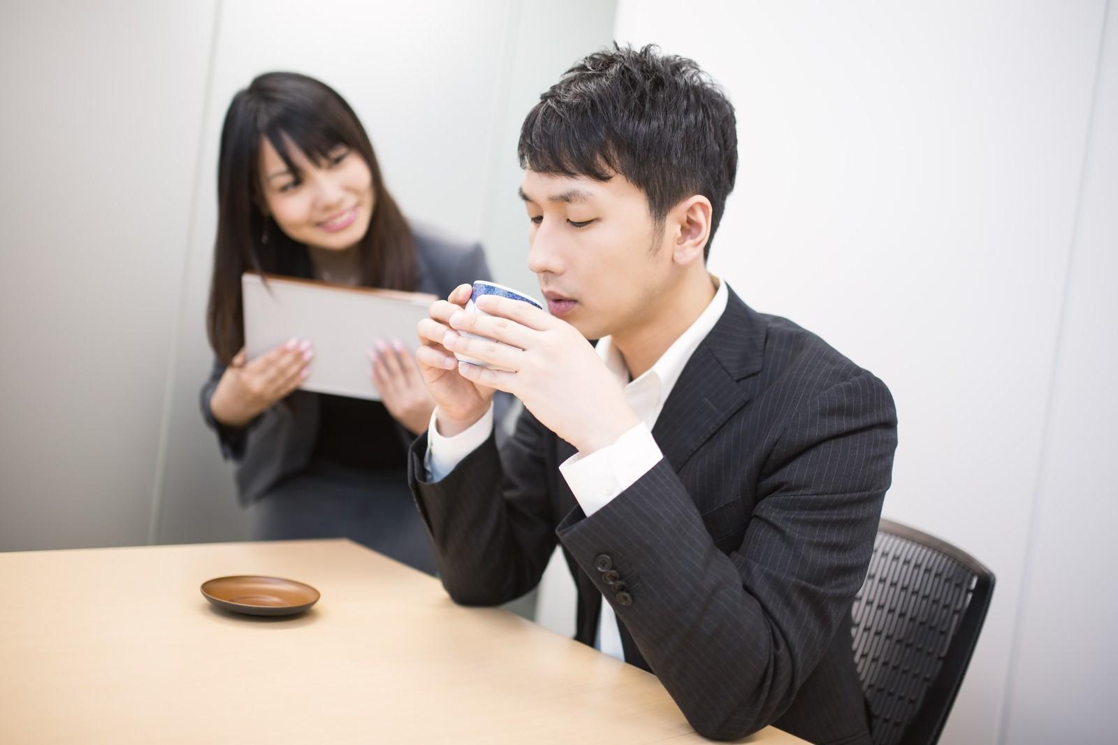 「女性社員に見つめられながらお茶をすするビジネスマン」[モデル:大川竜弥 Lala]
