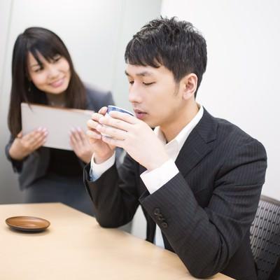 「女性社員に見つめられながらお茶をすするビジネスマン」の写真素材
