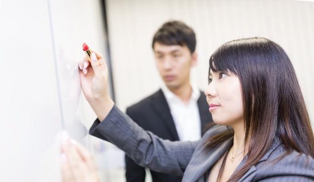 口紅でホワイトボードにメッセージを書く女性社員の写真