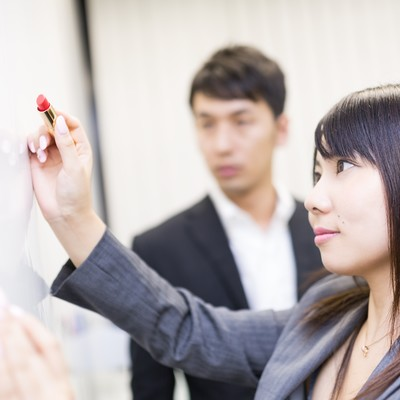 「口紅でホワイトボードにメッセージを書く女性社員」の写真素材