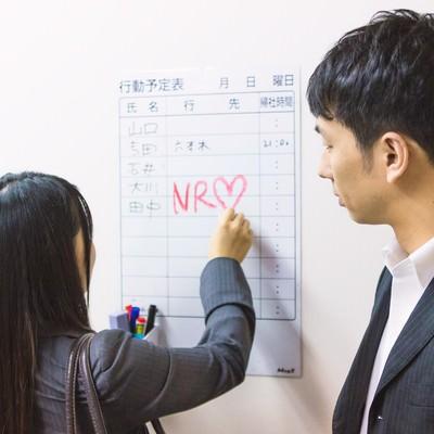 「NR(ノーリターン)と行動予定表に書き込む社内カップル」の写真素材