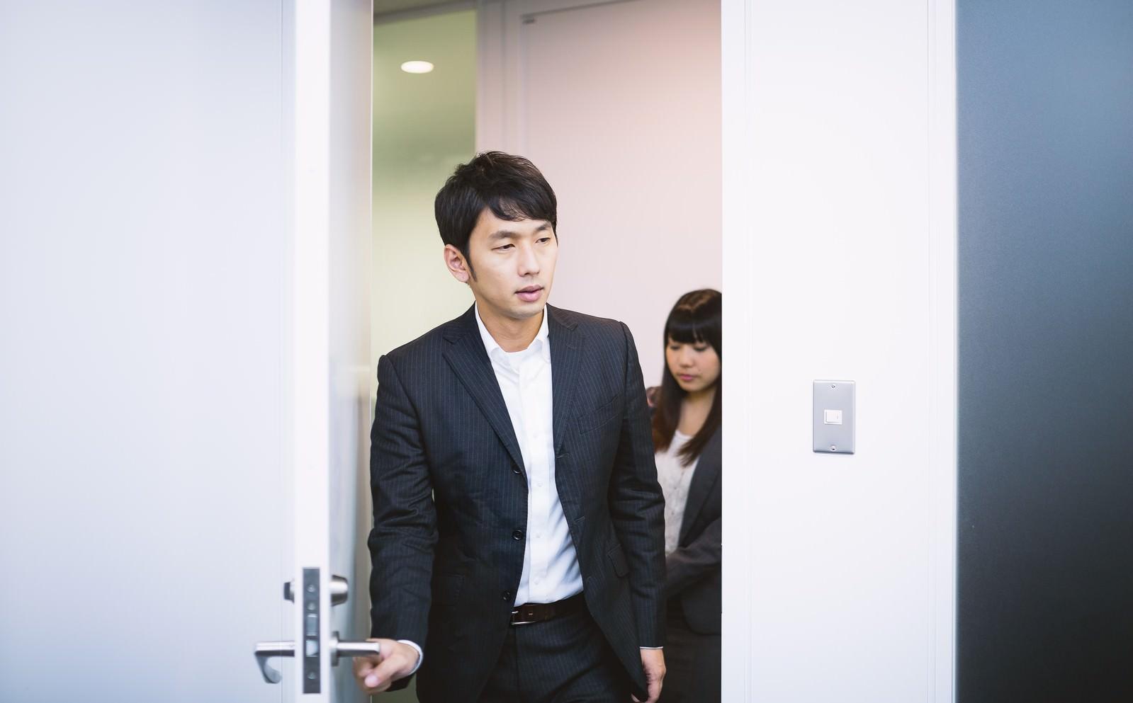 「新妙な面持ちで会議室のドアを開けるエリアマネージャー」の写真[モデル:大川竜弥 Lala]