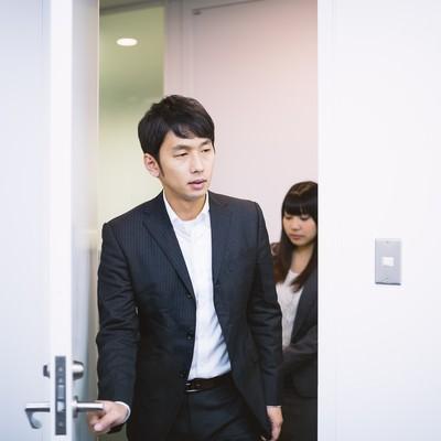「新妙な面持ちで会議室のドアを開けるエリアマネージャー」の写真素材