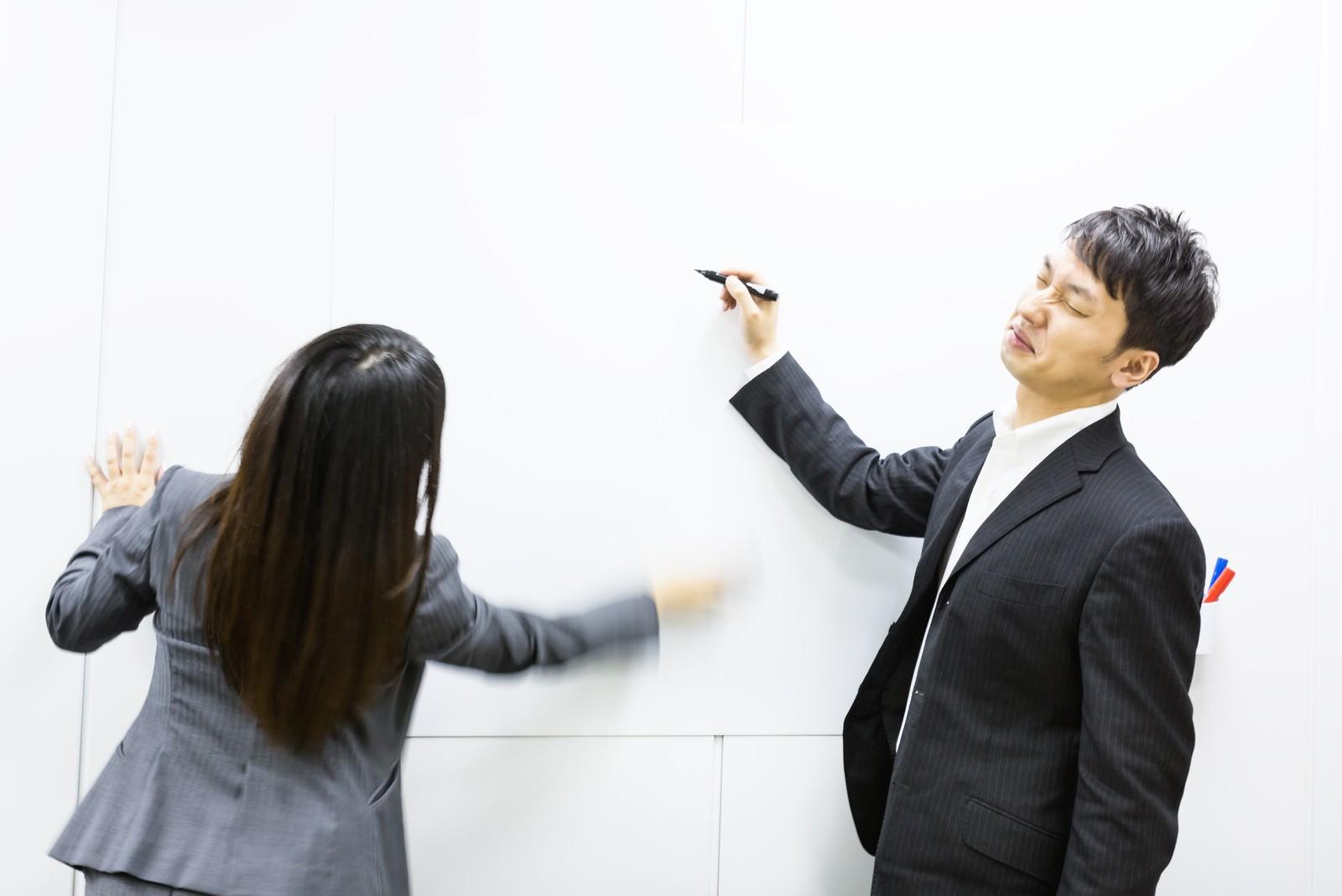「ホワイトボードに書いたマトリックス図を秒速で削除する女性」の写真[モデル:大川竜弥 Lala]