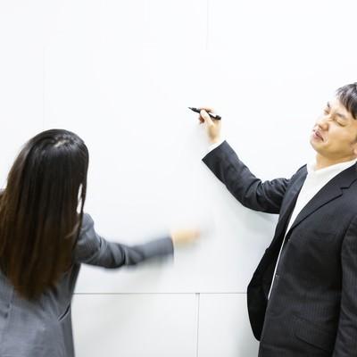 「ホワイトボードに書いたマトリックス図を秒速で削除する女性」の写真素材