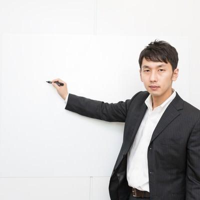 ホワイトボードを使ってプレゼンするホワイト企業の社員の写真