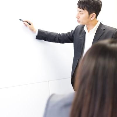 「社運をかけたプレゼンにペンを持つ手が震えるビジネスパーソン」の写真素材