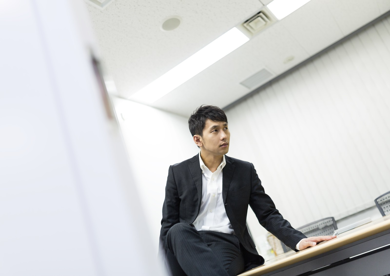 「会議室で部下のミスを執拗に責め立てる上司」の写真[モデル:大川竜弥]