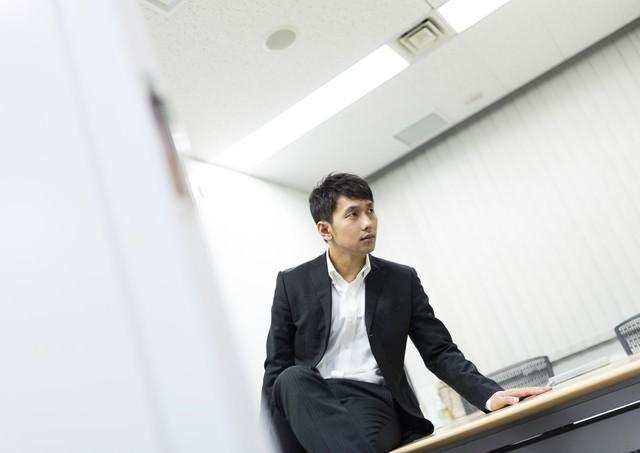 会議室で部下のミスを執拗に責め立てる上司の写真